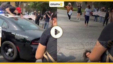 متظاهر أمريكي يقفز فوق سيارة