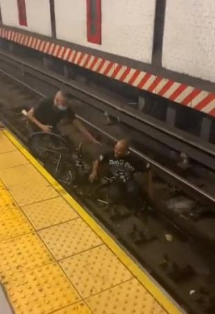 قبيل لحظات من وصول القطار.. إنقاذ رجل من ذوي الاحتياجات سقط مع كرسيه على شريط مترو بمحطة نيويورك - فيديو